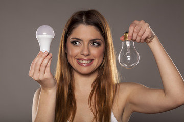 young smiling woman holding an old tungsten and new LED bulbs