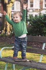 UK, England, Surrey, Boy ( 12-17 months ) standing on bench