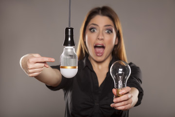 happy young woman holding an old, and shows the new LED bulb