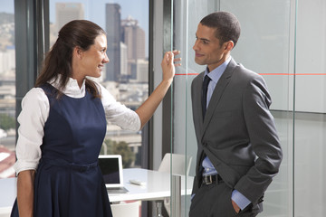 woman and man having discussion outside conference room