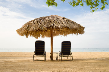 Jamaica, Sun loungers and beach umbrella by Caribbean Sea