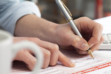 Close up of woman signing document