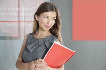 Woman standing in office holding folder, looking away