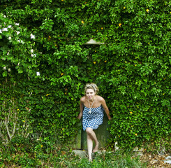 Croatia, Woman in ivy covering entire house
