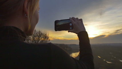 The young woman shoot the sunset panorama with the phone