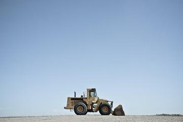 USA, Wyoming, Bulldozer against blue sky