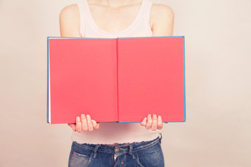 Woman holding book open to reveal blank pages
