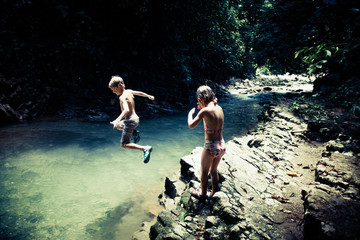 Costa Rica, Boy and girl (6-7) by river, boy jumping into water