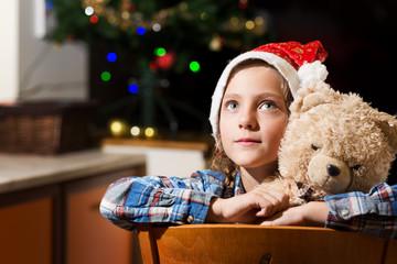 Girl (6-7) with teddy bear on Christmas Eve