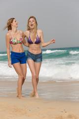 Junge Frauen lachend am Strand