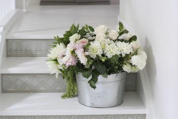 Bucket of cut flowers on steps