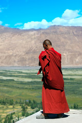 Buddhist monk against mountains in the Himalayas
