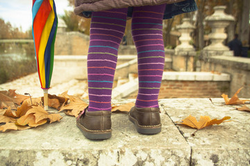 Girl's legs with colorful umbrella
