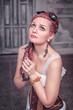 Beautiful steampunk woman in corset praying