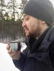 young man drink hot tea with pleasure at winter time