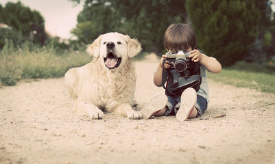 Boy (2-3) with his dog sitting and photographing with old camera