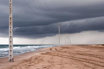 Postes eléctricos en la playa con tormenta al acecho