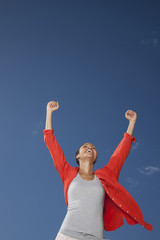 Woman with raised arms against blue sky