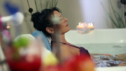 Pretty woman relaxing in jacuzzi with chapagne and hot water
