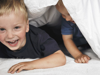 Two boys hiding under duvet