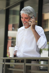 Businessman talking on the phone outdoors while holding coffee