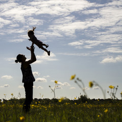 Silhouette of mother throwing son in air