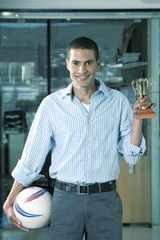 Business man in office holding soccer ball and trophy