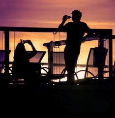 England, Southampton, Silhouettes of couple relaxing on balcony at sunset
