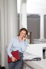 Portrait of female teacher in university building using mobile phone