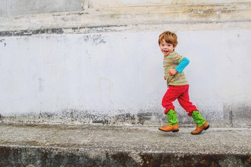 Boy (2-3) running against old wall