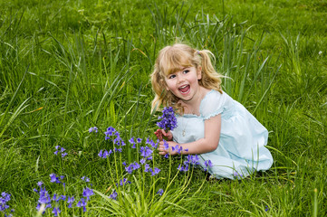 UK, Warwickshire, Rugby, Happy girl (4-5) picking up bluebells on meadow