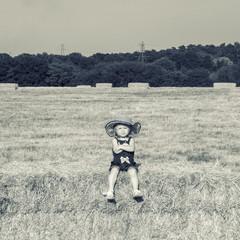Girl sitting on hay bale