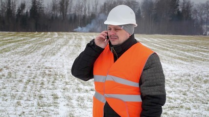 Forest inspector talking on a phone near smoke in the woods