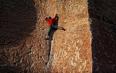 Rock climber works a sandstone slab with no rope or protection