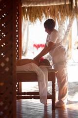 Woman giving a female customer body massage
