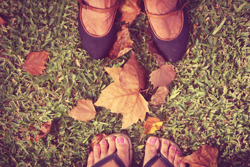 Two pairs of feet in autumn