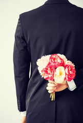 man hiding bouquet of flowers