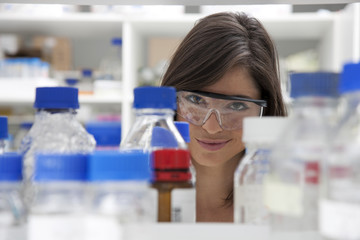 Woman looking through glass containers in research laboratory