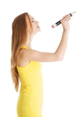 Side view of a woman with big crayon writing