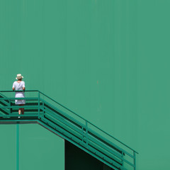 Woman with hat and big green wall