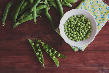 Fresh green peas on wooden table