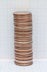 Stack of quarter dollar coins next to graph paper