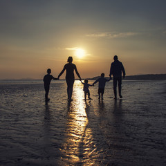 Silhouette of family holding hands on the beach at sunset