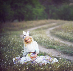 Young woman in dressed as bunny sitting in meadow