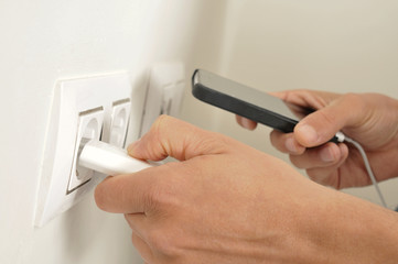 man plugging in the plug of his smpartphone in a socket