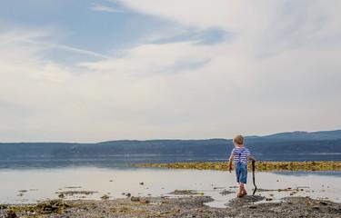 Boy (4-5) walking along lake