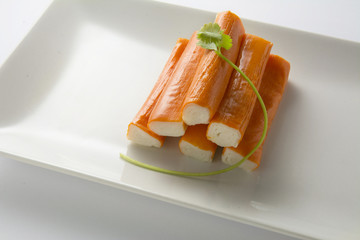 Surimi or crab sticks in a white rectangular plate. . White back