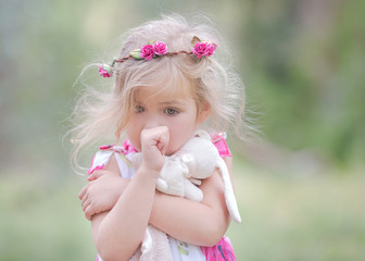 USA, Little girl (4-5) sucking thumb and clutching soft toy outdoors