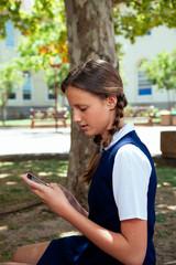 Teenage schoolgirl using phone outside school building