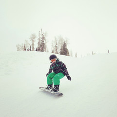 Boy snowboarding down hill